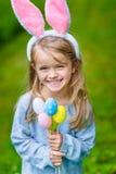 佩带桃红色兔子或兔宝宝耳朵的美丽的微笑的小女孩 库存图片
