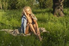 佩带桃红色女用贴身内衣裤和牛仔裤jacke的美丽的白肤金发的亭亭玉立的女孩 免版税库存图片