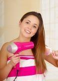 佩带桃红色毛巾和干燥的美丽的新鲜的女孩她的头发 免版税库存图片