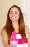 佩带桃红色毛巾和干燥的美丽的新鲜的女孩她的头发 库存图片