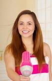 佩带桃红色毛巾和干燥的美丽的新鲜的女孩她的头发 库存照片
