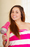 佩带桃红色毛巾的美丽的新鲜的女孩烘干她的头发 免版税库存图片