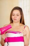 佩带桃红色毛巾的美丽的新鲜的年轻犹豫的女孩拿着烘干她的头发的剃刀 库存照片