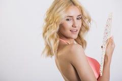 佩带桃红色游泳衣摆在的性感的白肤金发的妇女 免版税库存图片