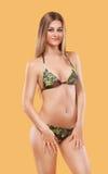 佩带桃红色游泳衣的性感的白肤金发的妇女摆在颜色背景 理想的机体 比基尼泳装编目 免版税库存照片