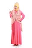 佩带桃红色穆斯林礼服指向的美丽的妇女 库存照片