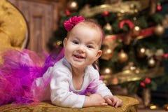 佩带桃红色裙子和红色头饰带的逗人喜爱的女婴,放置在圣诞树前面的长沙发 微笑的小孩 免版税库存图片