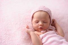 佩带桃红色,被编织的帽子的新出生的女婴 免版税库存图片