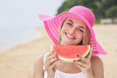 佩带桃红色sunhat用水多的西瓜的快乐的妇女 库存照片