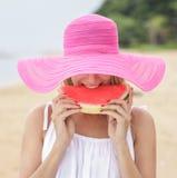 佩带桃红色sunhat的少妇吃新鲜的西瓜 免版税库存图片