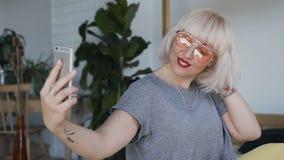 佩带橙色风镜和纹身花刺在她的手上的特写镜头A妇女移动她的白发并且拾起她的电话 一微笑 影视素材