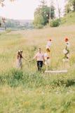 佩带淡紫色礼服花圈和英俊的人桃子衬衣的美丽的妇女走到摇摆户外 库存图片
