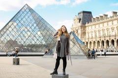 佩带灰色外套和身分的女孩在天窗和玻璃金字塔附近在巴黎 库存照片