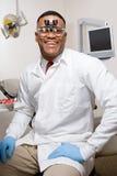 佩带牙齿双眼寸镜的牙医 免版税库存照片