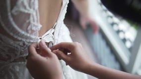 佩带用人工和系带美丽的白色婚纱的女傧相清早 妇女支持逗人喜爱 影视素材