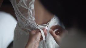 佩带用人工和系带美丽的白色婚纱的女傧相清早 妇女支持逗人喜爱 股票视频