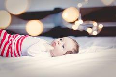 佩带白色的滑稽的矮小的婴孩在床上给躺下穿衣 免版税图库摄影