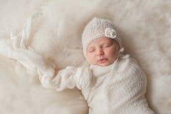 佩带白色被编织的帽子的新出生的女婴 库存照片