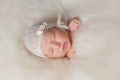 佩带白色被编织的帽子的新出生的女婴 库存图片