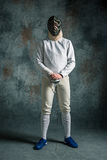 佩带的人操刀与剑的衣服反对灰色 图库摄影