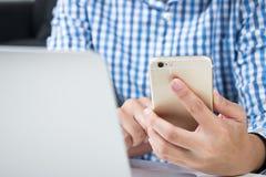 ?? 佩带的人蓝色衬衣为网络购物使用电话 免版税图库摄影