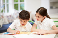 佩带的孩子做家庭作业在厨房里 免版税库存图片