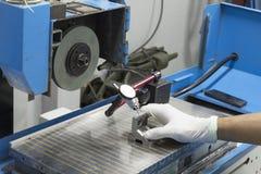 佩带的白色手套使用在磨床的指示器规格 库存图片