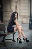 佩带短裙和高跟鞋的英俊的可爱的女孩站立外面在都市场面 库存图片