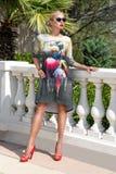 佩带礼服和高跟鞋和太阳镜立场的美丽的现象惊人的典雅的豪华性感的白肤金发的式样妇女 库存图片