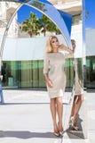 佩带礼服和高跟鞋,在惊人的看法的立场的美丽的现象惊人的典雅的豪华性感的白肤金发的式样妇女能 免版税库存照片