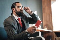 佩带精密企业服装和手手表的兴旺的人 免版税库存照片