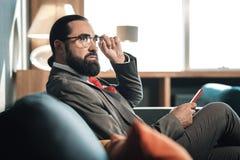 佩带精密企业服装和红色领带的时髦的有胡子的人 免版税库存照片