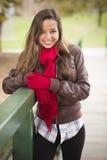 佩带红色围巾和手套的俏丽的妇女纵向外面 免版税库存图片