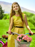 佩带红色圆点的女孩穿戴乘驾骑自行车入公园 库存照片