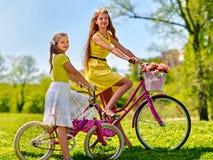 佩带红色圆点的女孩穿戴乘驾骑自行车入公园 免版税库存照片