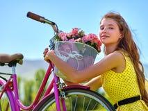佩带红色圆点的女孩穿戴乘驾骑自行车入公园 免版税库存图片