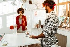 佩带红色头饰带的有胡子的人打与女朋友的网球 免版税库存图片