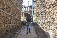 佩带红色夹克背包横穿山村的年轻俏丽的妇女 山迁徙的岩石道路 老城镇 免版税图库摄影