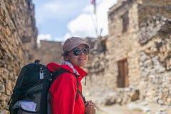佩带红色夹克背包横穿山村的画象年轻俏丽的妇女 山迁徙的岩石道路 老城镇 免版税库存照片