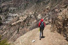 佩带红色夹克背包足迹山的年轻俏丽的妇女 山迁徙的岩石道路风景视图背景 免版税库存图片