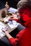 佩带红色毛线衣读书占卜卡片的有胡子的占卜者 免版税库存照片