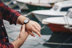 佩带红色的年轻时兴的人检查了衬衣和一块黑模式手表 街道一个典雅的时钟的样式细节 免版税库存照片