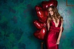 佩带红色礼服和红色气球心脏的女孩为Valentin塑造 免版税库存照片