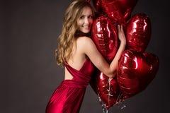 佩带红色礼服和红色气球心脏的女孩为Valentin塑造 免版税图库摄影