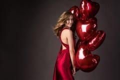 佩带红色礼服和红色气球心脏的女孩为Valentin塑造 免版税库存图片