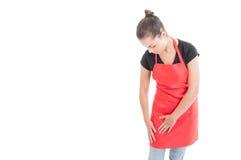 佩带红色围裙的年轻女性雇员在超级市场 图库摄影