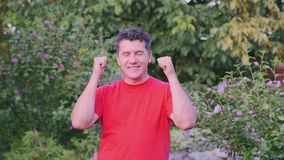佩带红色T恤杉打手势的微笑的中间年迈的人室外 影视素材