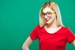 佩带红顶和镜片的微笑的惊奇的女孩画象  肉欲相当白肤金发与长的头发摆在  免版税库存图片