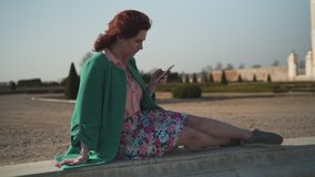佩带绿色被顶起的享用的太阳的时尚上瘾的年轻女人在宫殿前面的一个喷泉 股票视频