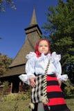 佩带罗马尼亚传统衣物和传统木教会背景的小女孩 库存图片